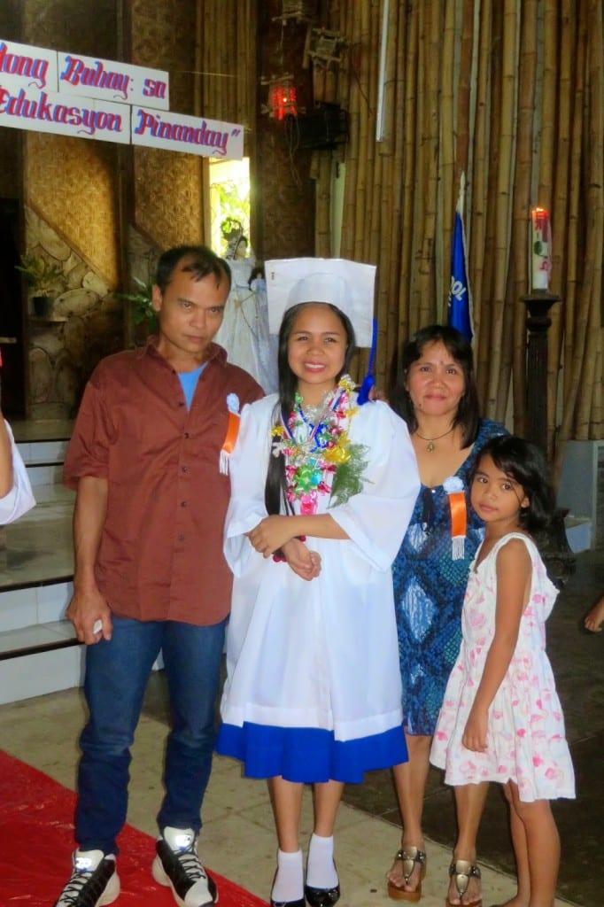 Elza, class salutatorian, and her proud parents at graduation.